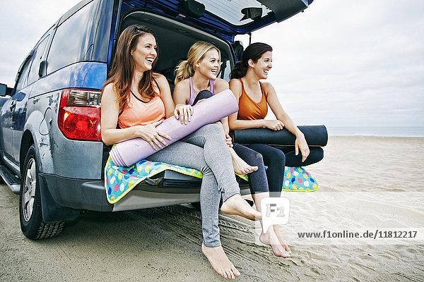 Caucasian women sitting in hatch of car on beach
