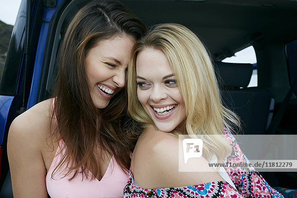 Laughing Caucasian women in hatch of car