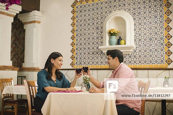 Hispanic couple toasting with wine in restaurant
