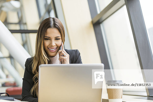 Mixed Race businesswoman talking on cell phone and using laptop