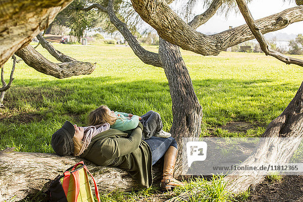 Caucasian mother and daughter laying on tree branch