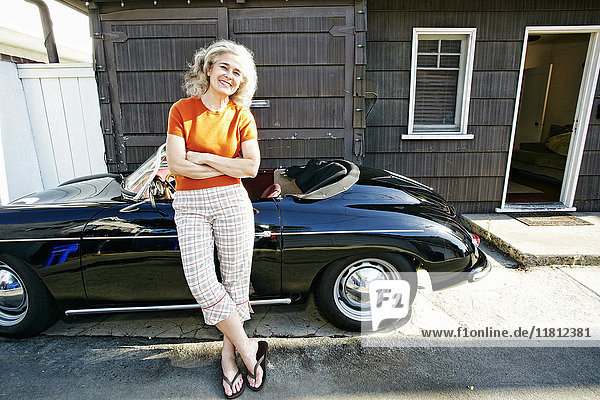 Portrait of older Caucasian woman leaning on convertible car