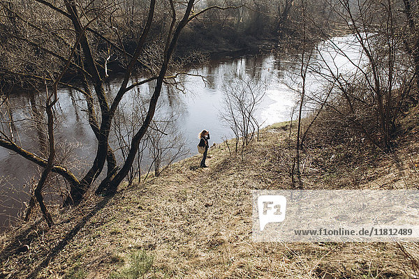Distant woman standing near river