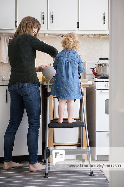 Caucasian girl standing on ladder cooking with mother in kitchen