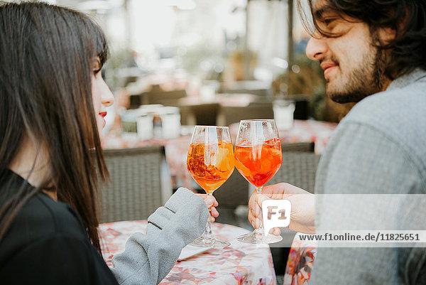 Junges Paar sitzt vor einem Café  hält Getränke in der Hand und spricht einen Toast aus
