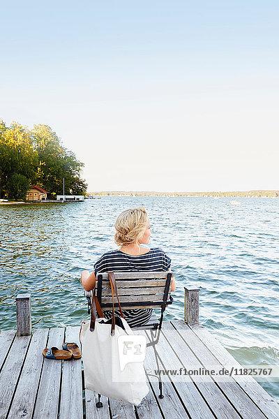 Frau sitzt auf Pier am Wasser