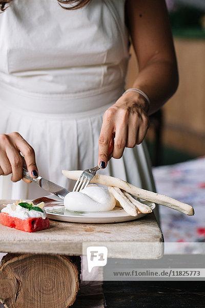Frau bereitet vegetarisches Gericht auf einem Schneidebrett zu