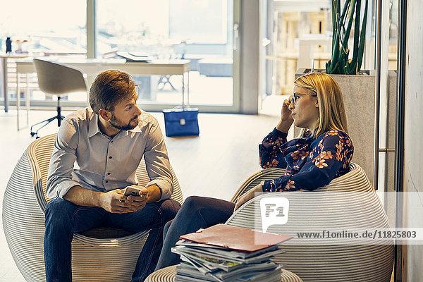 Geschäftsfrau im Gespräch mit einem männlichen Kollegen im Lounge-Bereich