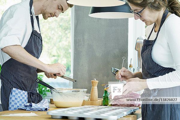 Zwei Köche arbeiten am Tisch und bereiten das Essen vor