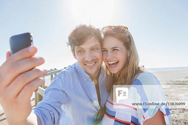 Ehepaar am Strand beim Selbstfotografieren