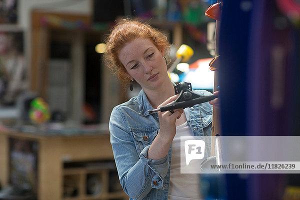 Woman working in skateboard shop  inspecting skateboard trucks