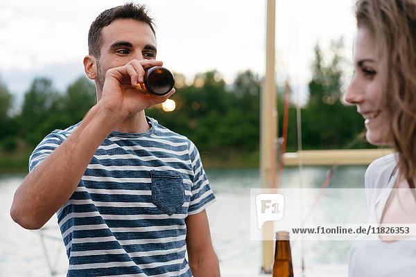 Mann und Frau auf dem Pier  entspannen sich  halten Bierflaschen