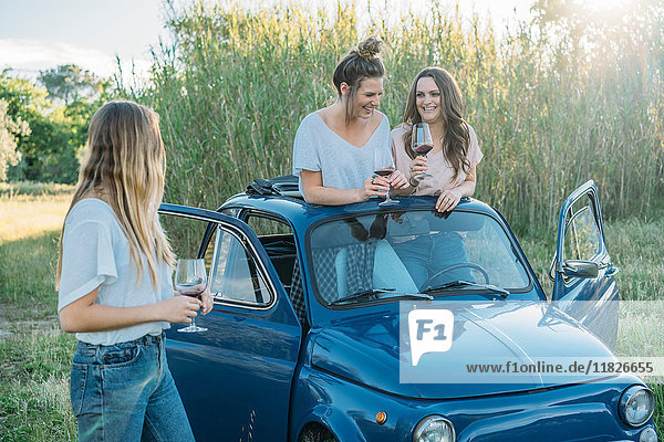 Friends drinking wine by vintage car  Firenze  Toscana  Italy  Europe