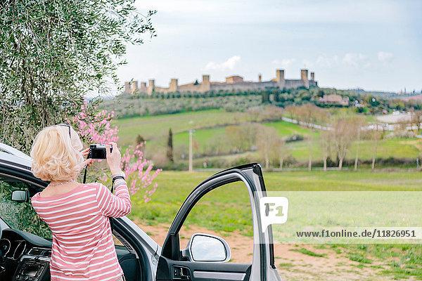 Rückansicht einer Touristin  die eine Festung in der Landschaft fotografiert  Siena  Toskana  Italien