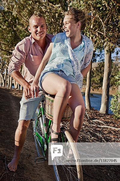 Junge Frau sitzt vor dem Fahrrad ihres Freundes