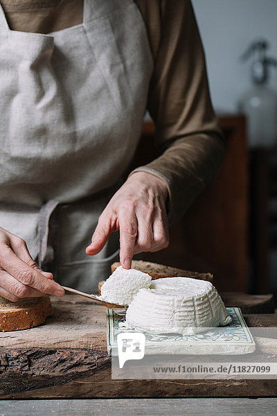 Woman taking slice from whole ricotta  mid section