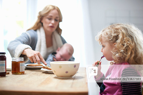 Mother holding baby boy  sitting at kitchen table with young daughter  having breakfast