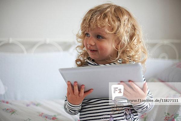 Kleines Mädchen benutzt digitales Tablett am Bett