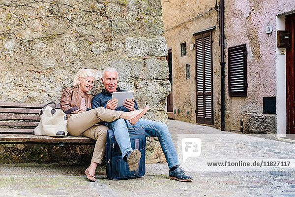 Touristenpaar sitzt auf Bank und betrachtet digitales Tablet in Siena  Toskana  Italien