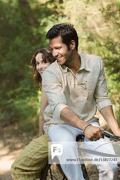 Paar sitzt auf dem Fahrrad und lächelt