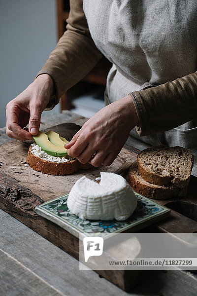 Woman placing slices of avocado onto sliced bread with ricotta  mid section
