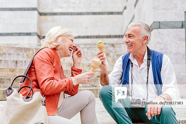 Touristenpaar beim Essen von Eiswaffeln und Lachen in Siena  Toskana  Italien