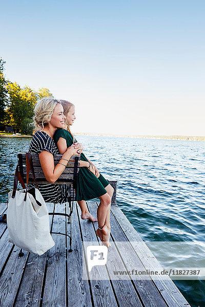Mutter und Tochter sitzen auf dem Pier am Wasser