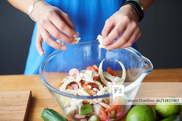 Hände einer jungen Frau am Küchentisch zerbröseln Feta in Salatschüssel