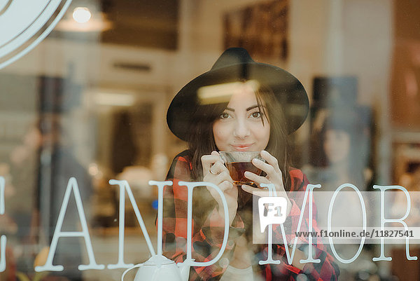 Portrait of young woman sitting in cafe  view through window
