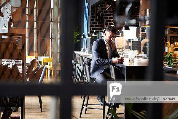 Enttäuschter Mann schaut auf Smartphone  während er an der Bar sitzt