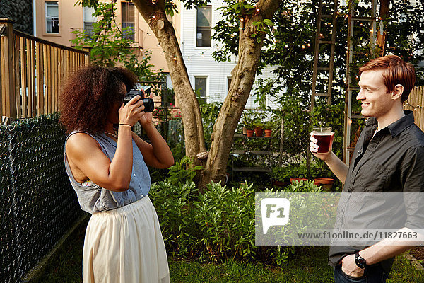 Junge Frau fotografiert Mann im Garten