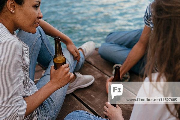 Drei Freunde entspannen sich am Pier und halten Bierflaschen