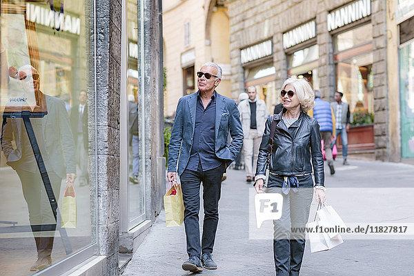 Touristenpaar schlendert mit Einkaufstaschen auf der Straße in der Stadt  Siena  Toskana  Italien