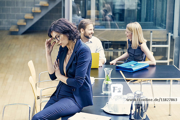 Businesswoman sitting contemplating on boardroom table