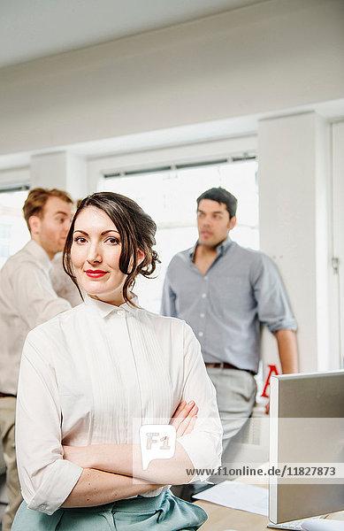 Porträt einer Büroangestellten  männliche Kollegen im Hintergrund