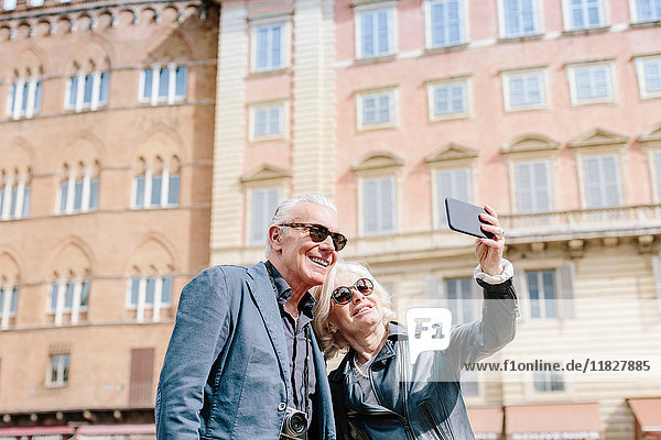 Tourist couple taking smartphone selfie in city  Siena  Tuscany  Italy