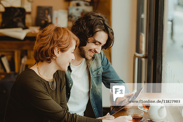 Young couple sitting in cafe  looking at digital tablet