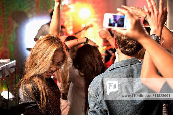 Teenager fotografieren Band mit Kamerahandys bei Konzert