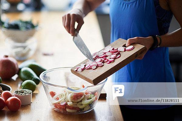 Mittelteil einer jungen Frau am Küchentisch bei der Zubereitung von in Scheiben geschnittenem Rettich
