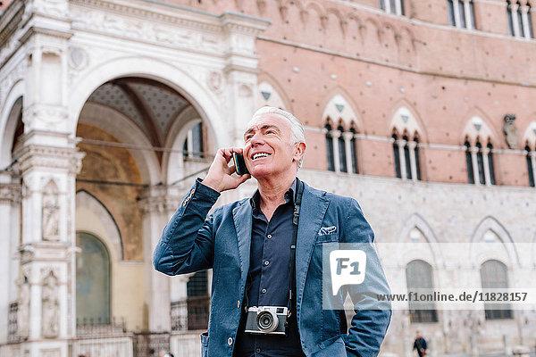 Älterer Mann telefoniert mit einem Smartphone in der Stadt  Siena  Toskana  Italien