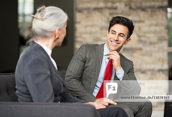 Geschäftsmann und -frau treffen sich auf einem Bürosofa