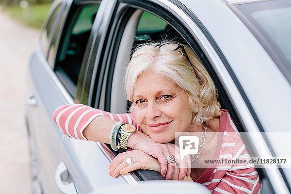 Porträt einer reifen Frau  die am Straßenrand aus dem Autofenster schaut