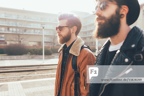 Side view of two young male hipster friends wearing sunglasses in city housing estate
