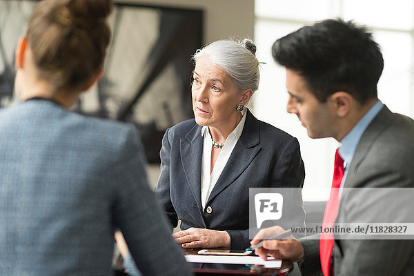 Businessman discussing with female colleagues in boardroom meeting