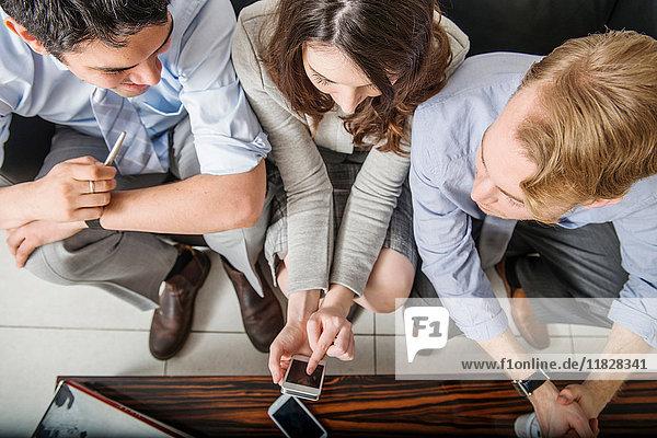 Bürokollegen mit Mobiltelefon  hoher Winkel