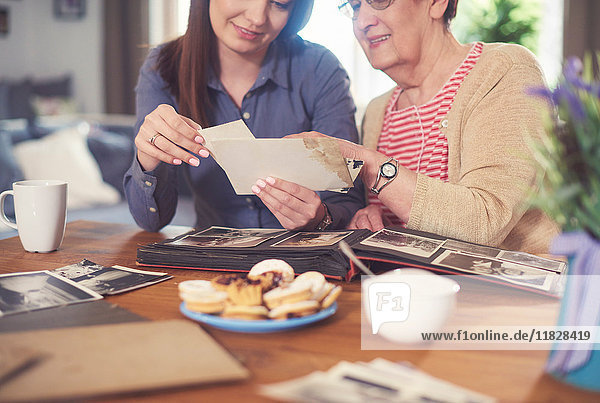 Junge Frau bei Tisch mit Großmutter  die sich alte Fotos ansieht