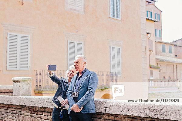 Touristenpaar mit Smartphone-Selfie in der Stadt  Siena  Toskana  Italien