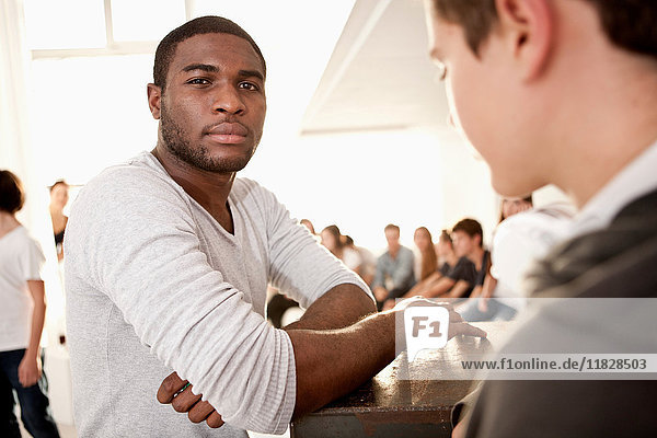 Group of friends at house party  young man looking at camera