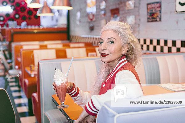 Porträt einer reifen Frau in Baseballjacke mit Milchshake im Diner der 1950er Jahre