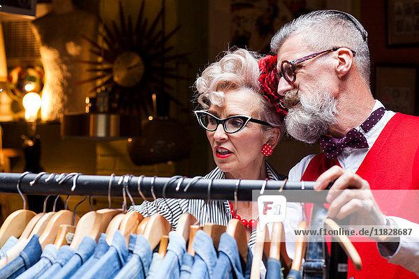 Schrulliges Vintage-Paar betrachtet Kleiderstange in Antiquitäten- und Vintage-Geschäften
